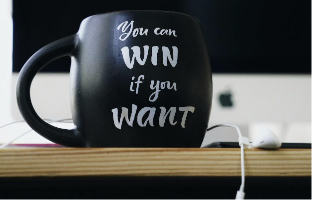 "black coffee mug sitting on a desk that reads ""you can win if you want"""